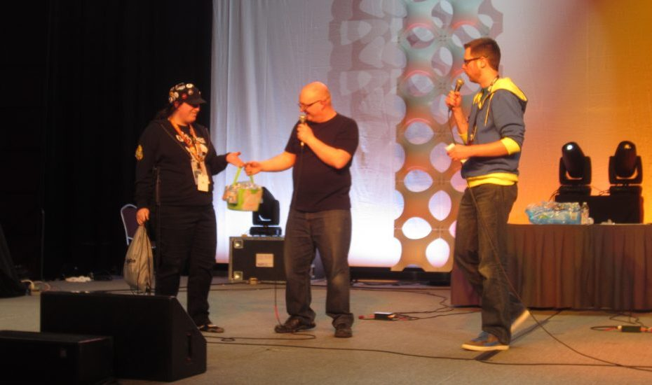 Ransim on stage at PAX East 2013 handing off the Child's Play donations and a easter basket to Mike and Jerry
