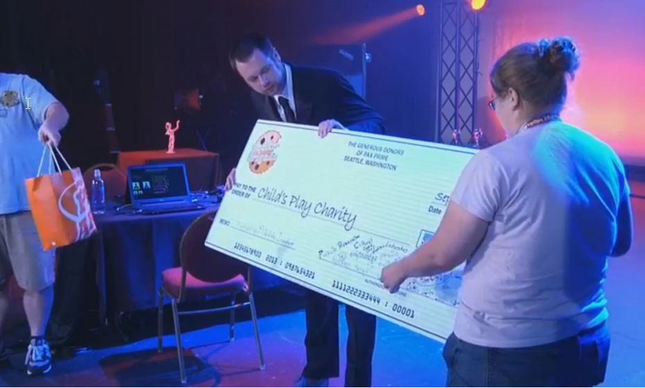 Brigade volunteers handing over a giant check at PAX West on stage.
