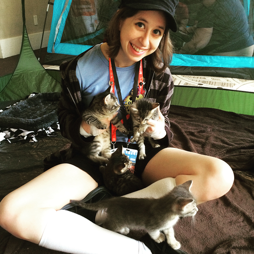 Sam Coccetti aka Samala posing with four kittens in a tent